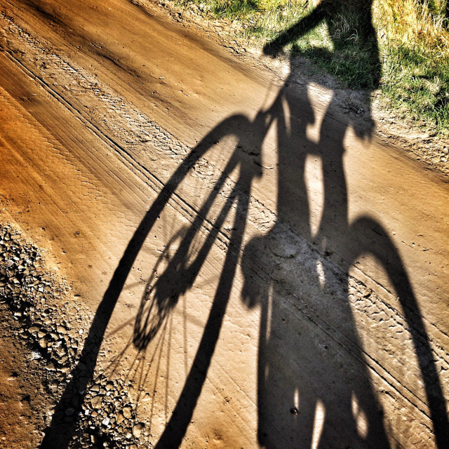 """""""Mountain bike rider shadow on a dirt track"""" stock image"""