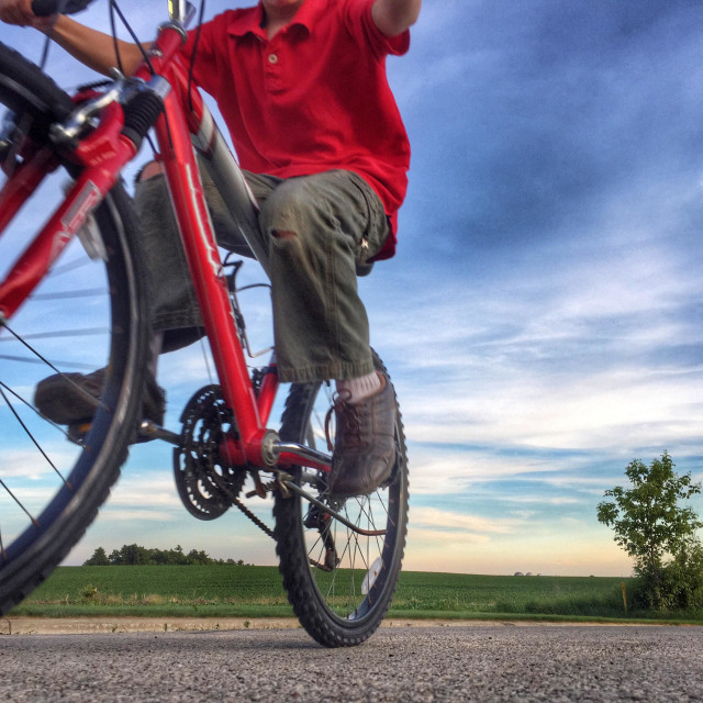 """""""View looking up at a boy riding past on his red bicycle"""" stock image"""