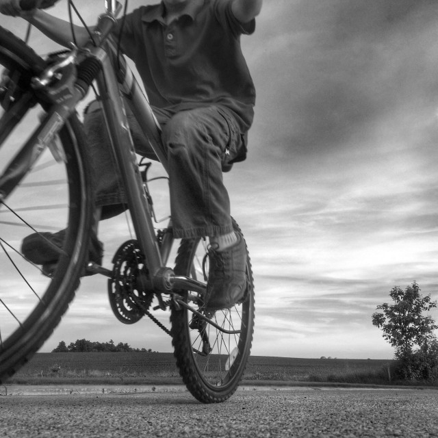 """""""Black and white image of a person riding past on a bicycle"""" stock image"""