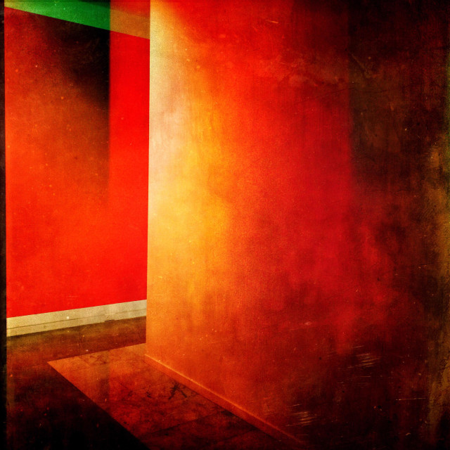 """""""Corner in a red hallway with play of light and texture on the walls."""" stock image"""