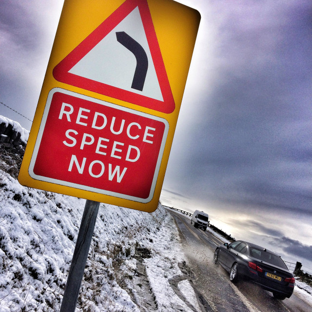 """Driving in snow reduce speed bend ahead"" stock image"