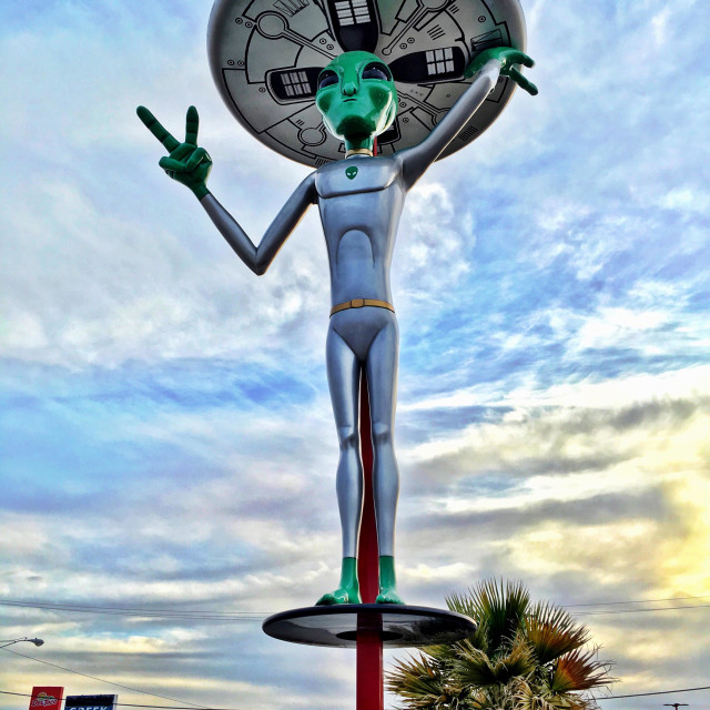 """Alien with a UFO gives the peace sign to traffic driving by in Baker, California USA ""We come in peace""."" stock image"