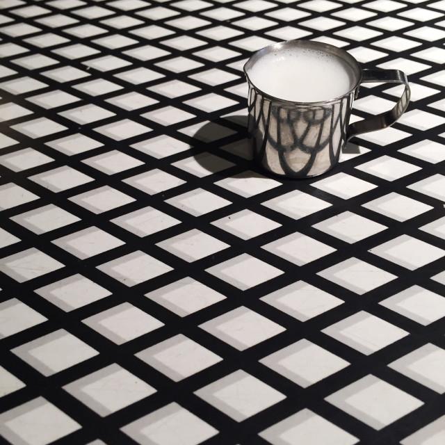 """Jug full of milk on geometric patterned background"" stock image"