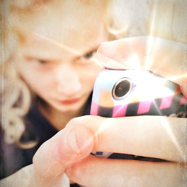 """""""Young girl taking flash photo with iPod"""" stock image"""