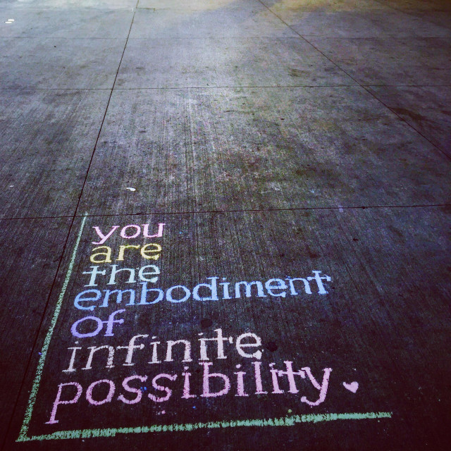 """You are the embodiment of infinite possibility inspirational quote on pavement in NYC"" stock image"