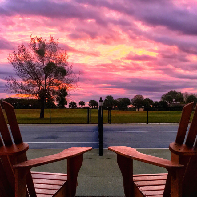 """""""Adirondack chairs overlook a tennis court during a colorful sunrise early in the morning."""" stock image"""