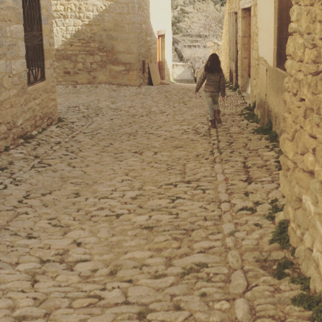 """""""Girl walking away in an empty street in the old village of Mirambel, in the province of Teruel, Spain"""" stock image"""
