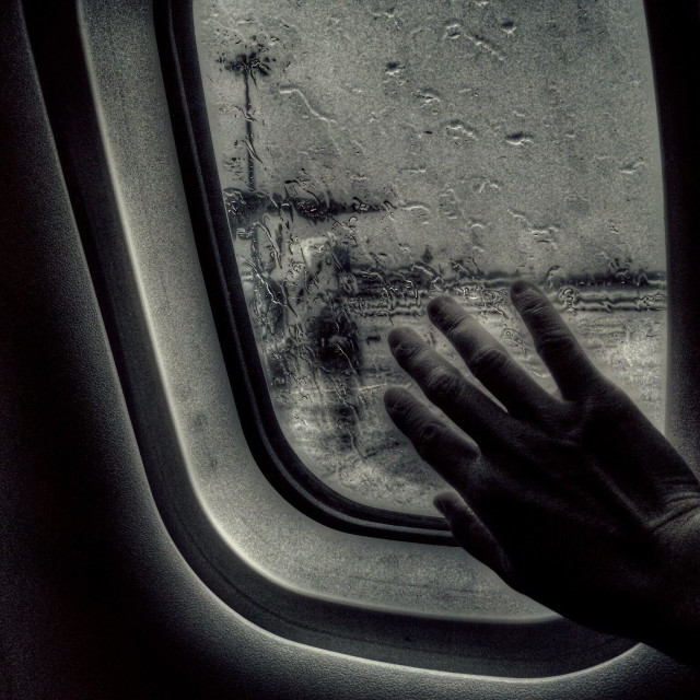 """""""My hand touching the plane window on a rainy day"""" stock image"""