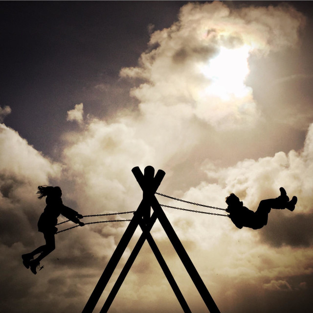 """""""Children play on a swing in a holiday park at Loch Ken, Scotland."""" stock image"""