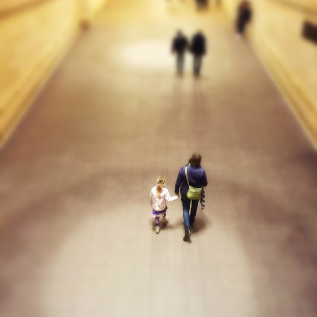 """A mother and daughter are holding hands walk up a ramp in Grand Central terminal, New York City"" stock image"