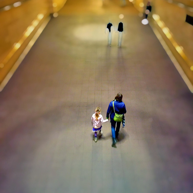 """A mother and daughter are holding hands and walking up a ramp in Grand Central terminal, New York City"" stock image"
