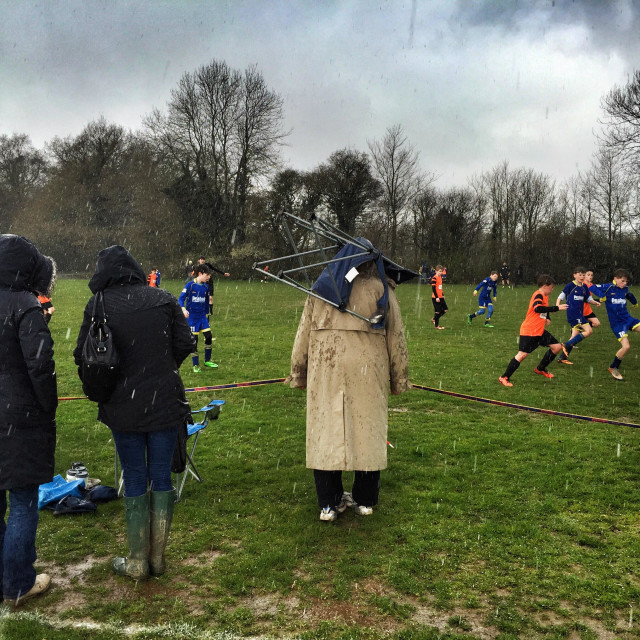 """A spectator puts a chair over his head to shelter from the rain as he watches a game of youth football in Petersfield, England."" stock image"