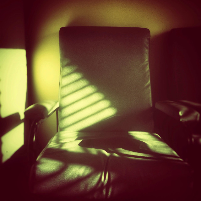 """Armchair in the blinds shades."" stock image"