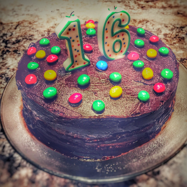 """""""Sixteenth Birthday cake. Home made chocolate cake with colourful candy and candles."""" stock image"""