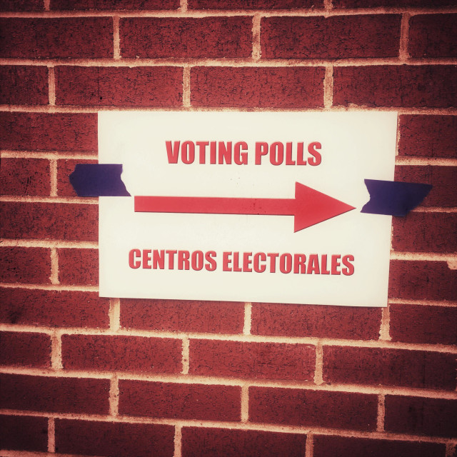 """Voting Polls sign in English and Spanish"" stock image"