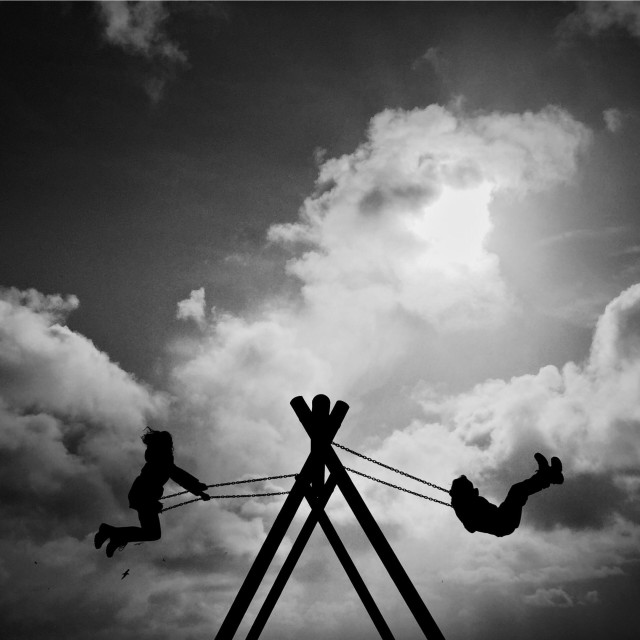 """""""Children play on a swing while on holiday in Galloway, Scotland."""" stock image"""