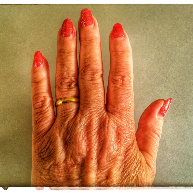 """Hard worked female hand with sparkly red nail polish and gold wedding band"" stock image"