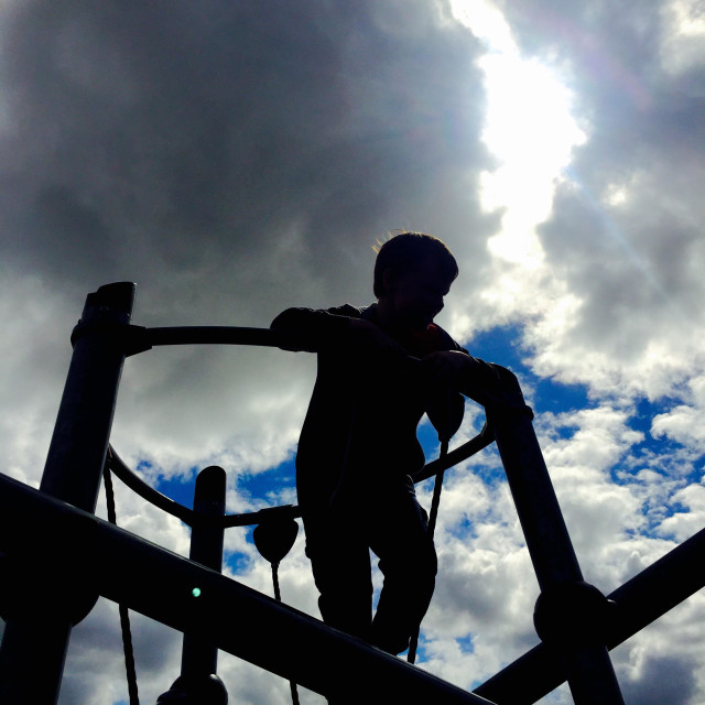 """Boy silhouette on climbing frame"" stock image"