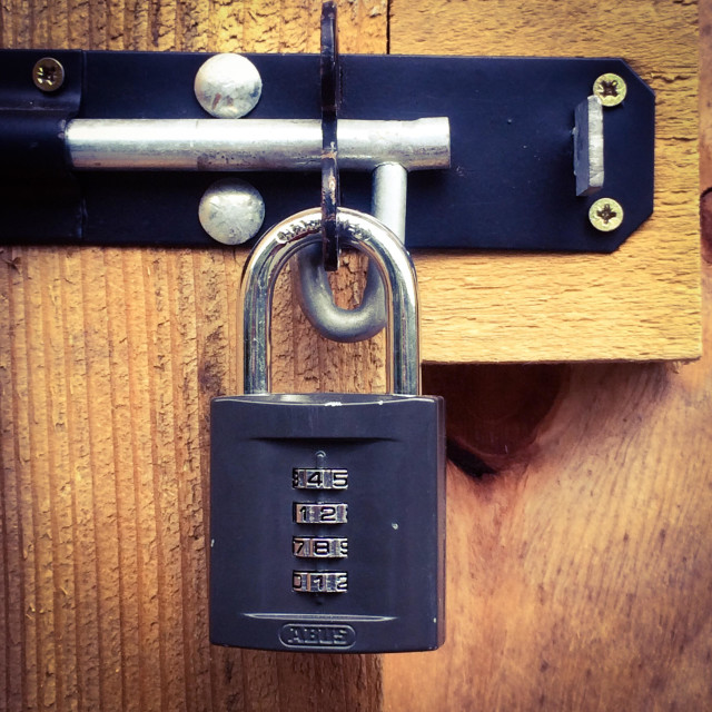 """""""Close up view of a padlock with a combination lock on a wooden door"""" stock image"""