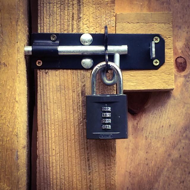 """Padlock with combination lock on a wooden door"" stock image"