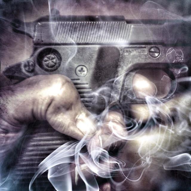 """""""Finger on trigger of smoking gun"""" stock image"""