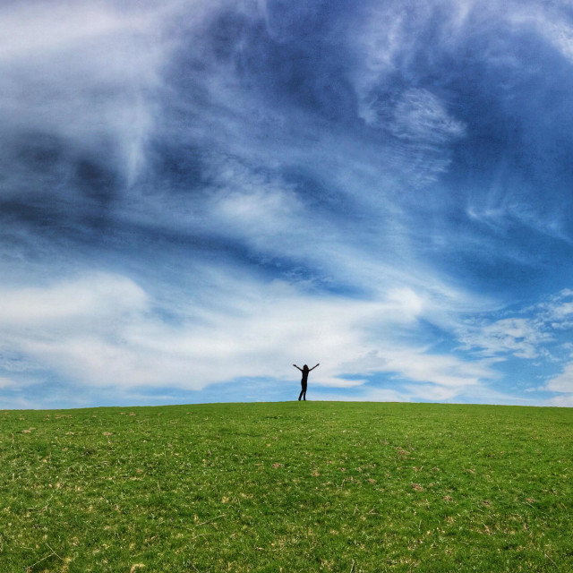 """Silhouetted figure with arms held high on horizon of gently rolling grass covered field and blue sky"" stock image"