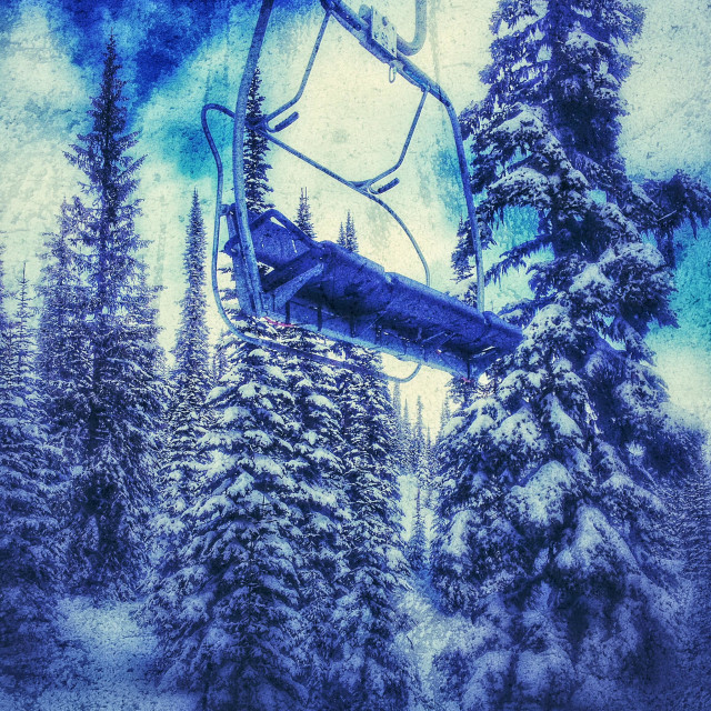 """Empty ski chair lift amongst snow covered trees."" stock image"