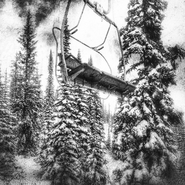 """Empty ski lift amongst snow covered trees. In black and white."" stock image"