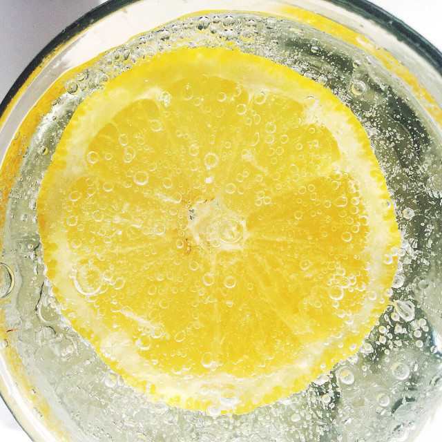 """""""A slice of lemon floating in a glass of carbonated mineral water. Photographed from above."""" stock image"""