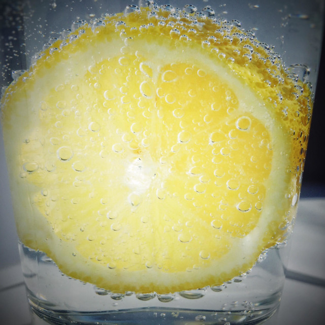 """""""Close up of a glass of fizzy water with a slice of lemon."""" stock image"""