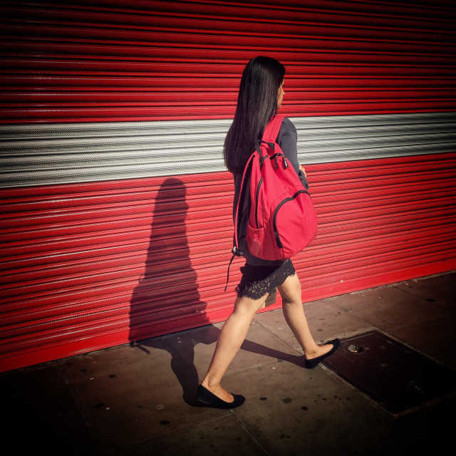 """""""Woman walking in an urban bright red and stripy setting"""" stock image"""