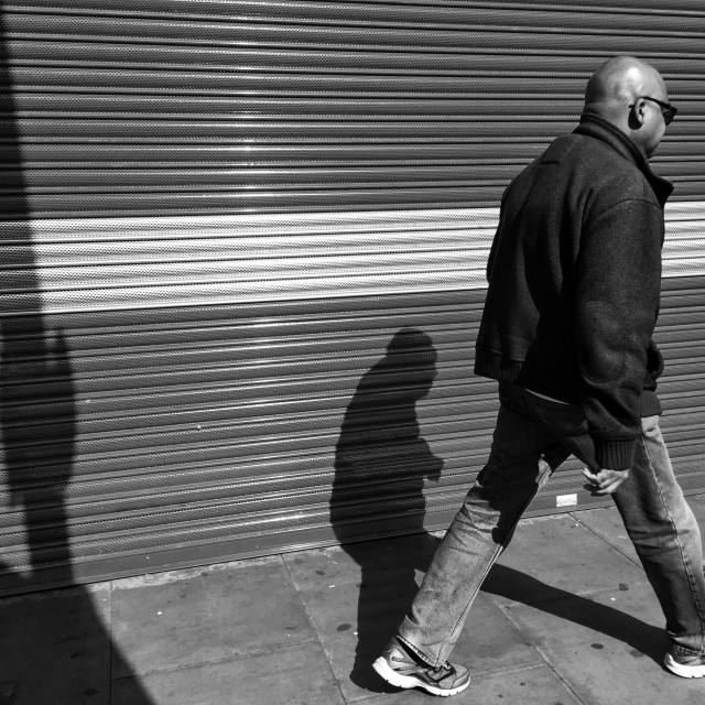 """""""Man walking in an urban setting by stripy shutters and shadows"""" stock image"""