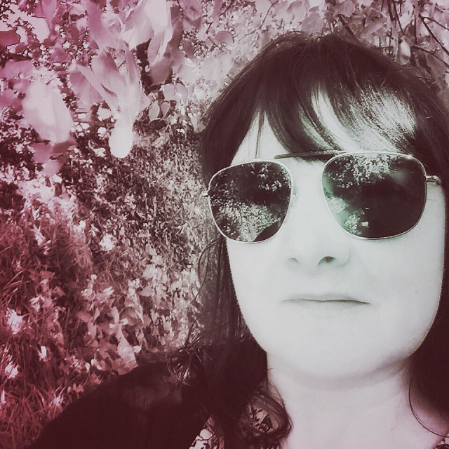 """Selfie of woman against Spring hedgerow."" stock image"