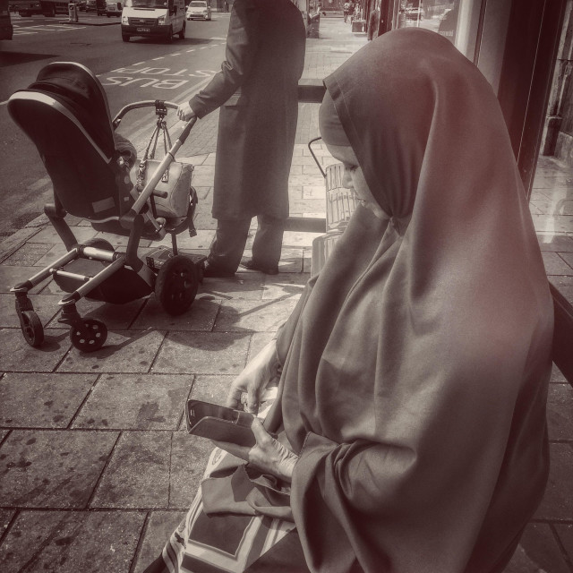 """""""Street Scene in multicultural London. Orthodox Jewish man with pram and Muslim woman in hijab on mobile phone"""" stock image"""