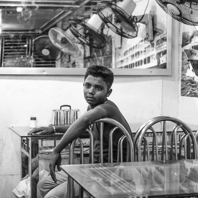 """Child worker sitting desperate in restaurant"" stock image"
