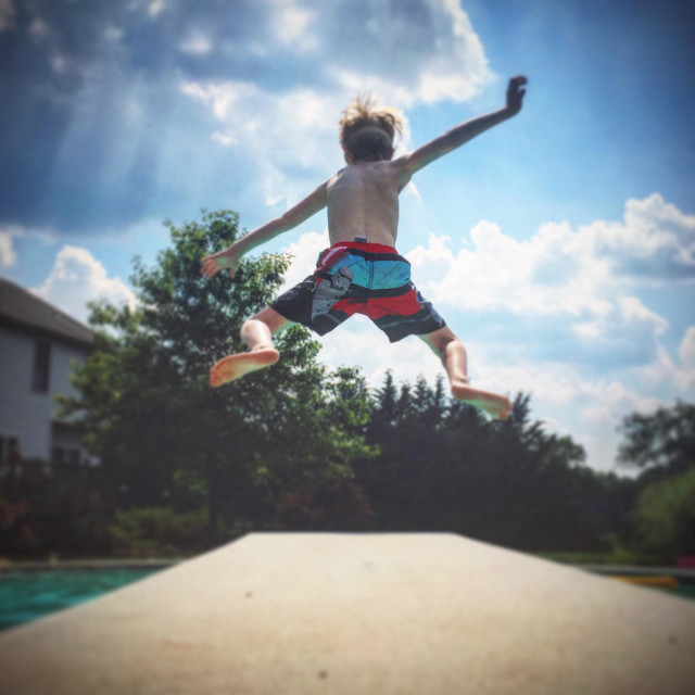 """""""A young boy jumps off a diving board and into a swimming pool on a hot summer day"""" stock image"""