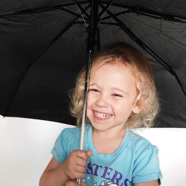 """Happy little girl with umbrella"" stock image"