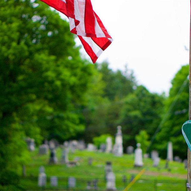 """Heart shaped reminder of the Sandy Hook tragedy is fixed to a pole in foreground with cemetery in background."" stock image"