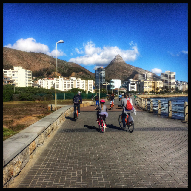 """""""Family cycling along the Seapoint promenade, Cape Town."""" stock image"""