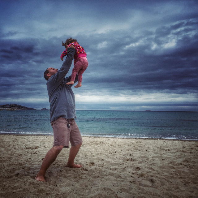 """""""Father holding his daughter on the beach"""" stock image"""