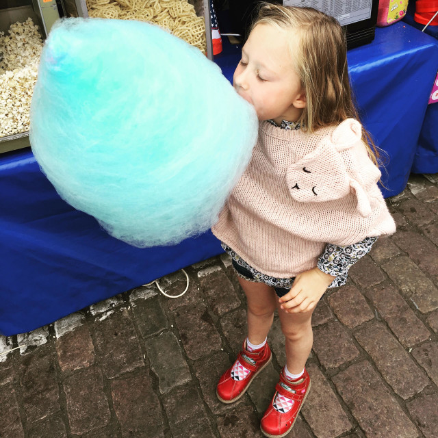 """Girl eating blue candy floss"" stock image"