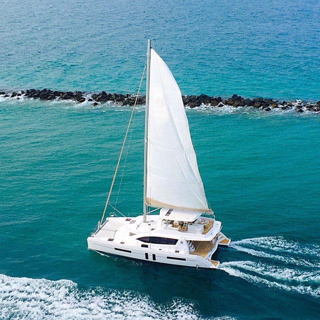 """""""Boat with Sail Up Cruising the Blue Ocean"""" stock image"""