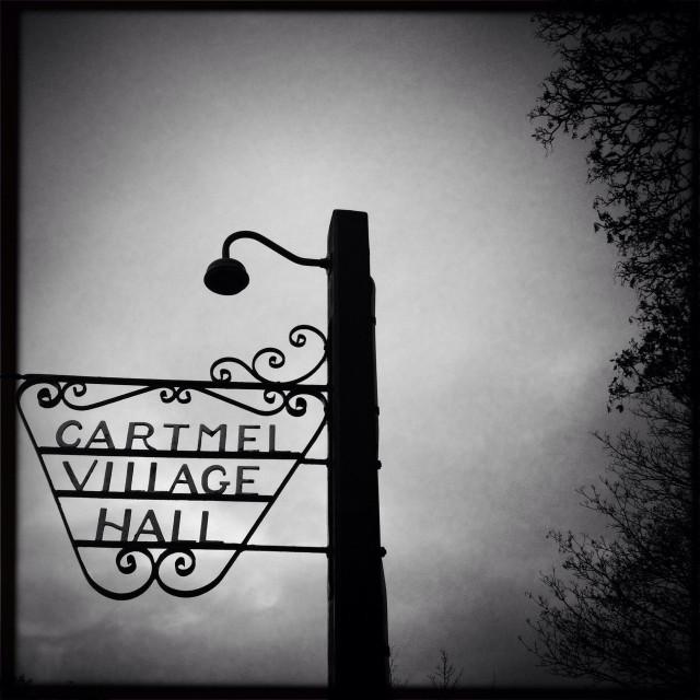 """Wrought iron sign and lamp post, Cartmel village hall, Cumbria"" stock image"