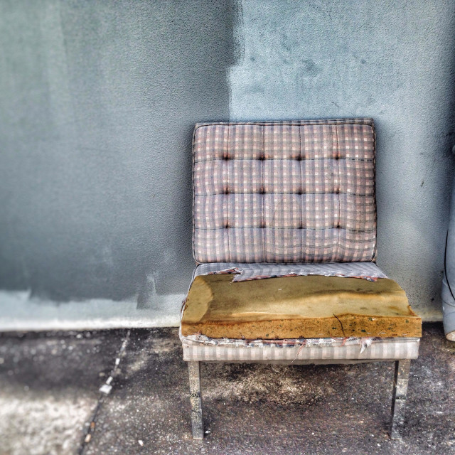 """Old dilapidated armchair against a wall."" stock image"