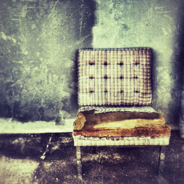 """Abandoned armchair against a wall."" stock image"