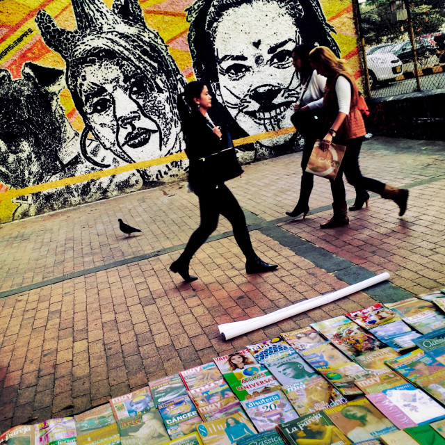 """Colombian women walk in front of a graffiti stencil artwork, created by an artist named Dj Lu, in the center of Bogotá, Colombia, 16 February, 2016."" stock image"