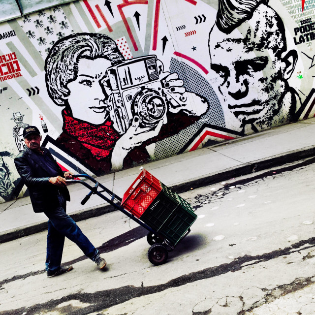 """A Colombian street vendor passes in front of a graffiti stencil artwork, created by an artist named Toxicómano Callejero, in the center of Bogotá, Colombia, 13 March, 2016."" stock image"