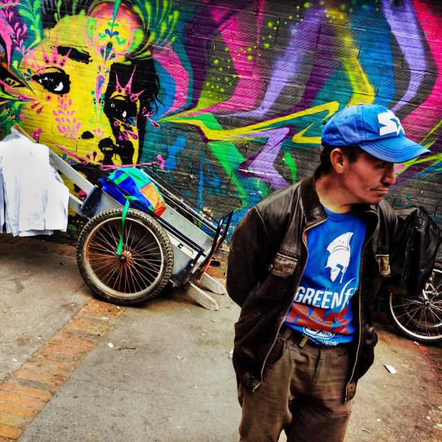 """A Colombian street vendor stands in front of a graffiti artwork, created by an artist named Stinkfish, in the center of Bogotá, Colombia, 21 February, 2016."" stock image"