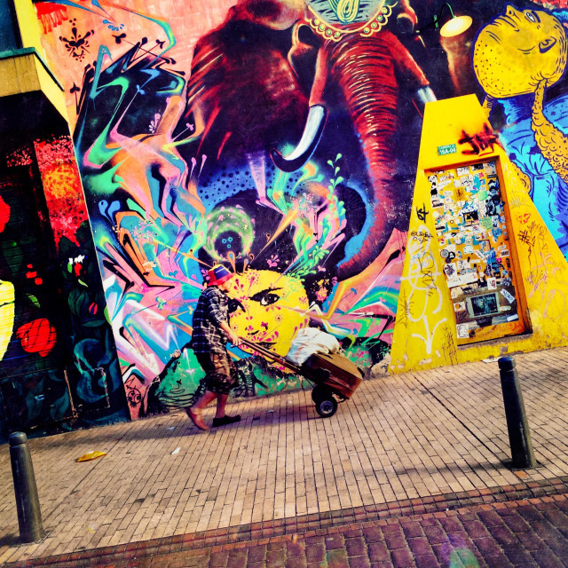 """A Colombian street vendor passes in front of a graffiti artwork, created by an artist named Stinkfish, in La Candelaria, Bogotá, Colombia, 14 February, 2016."" stock image"