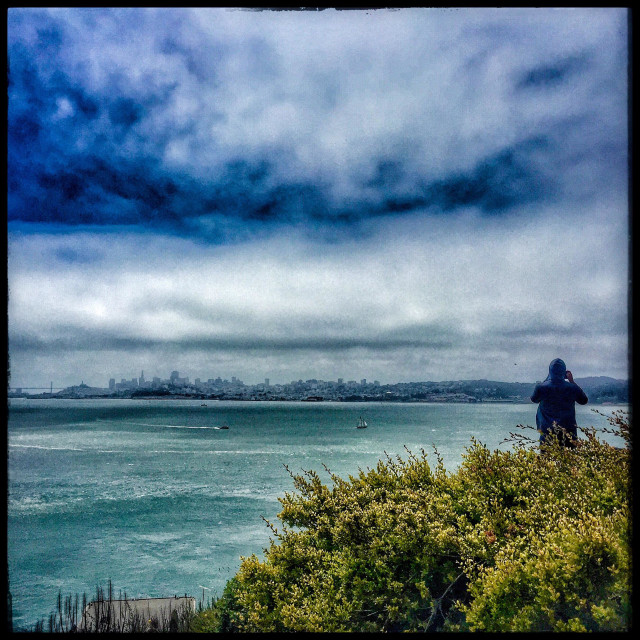 """Man taking photo of San Francisco cityskape"" stock image"